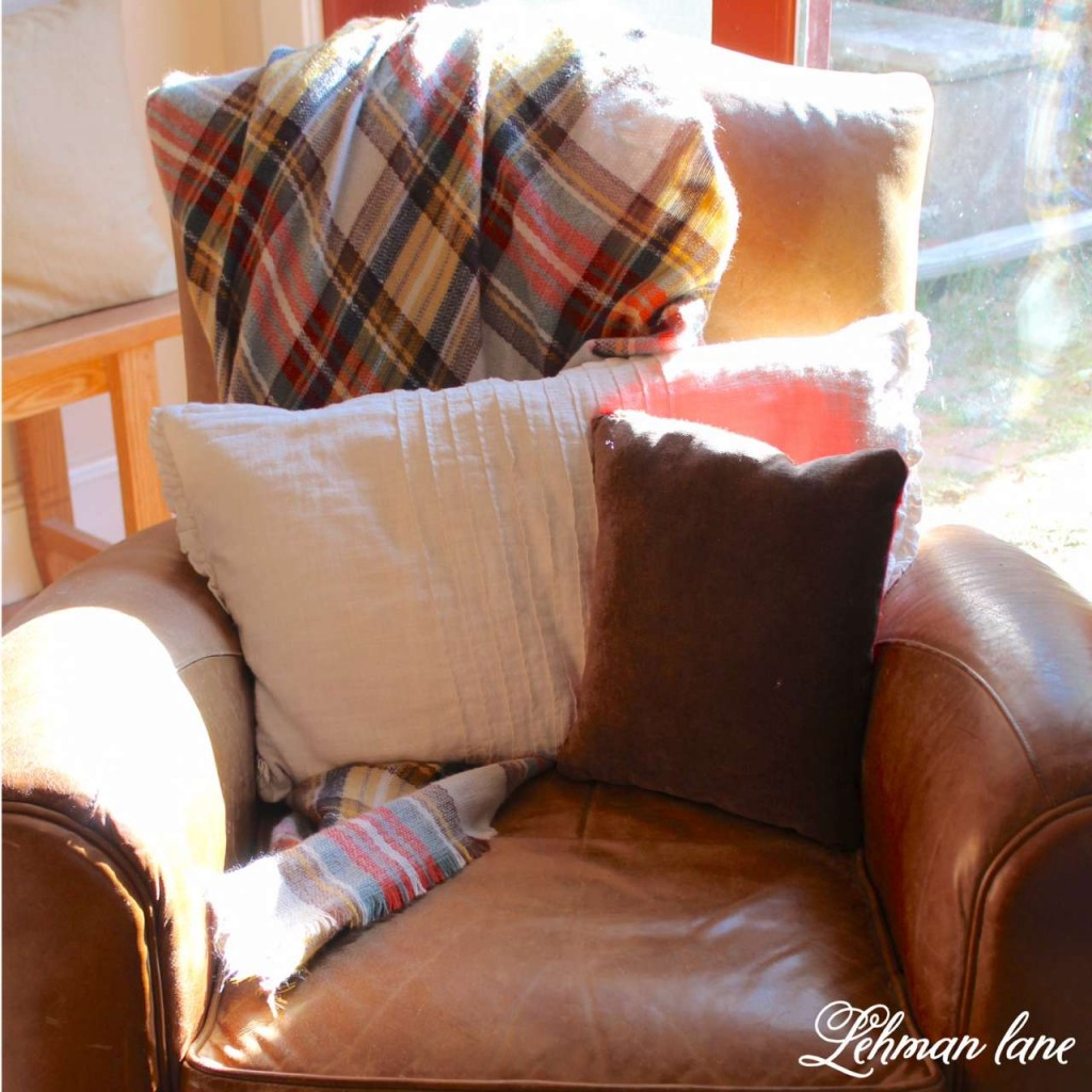 8 tips to decorate for fall on a budget / leather chair, plaid throw