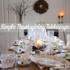 Thanksgiving tablescape, white dishes, farm table, clear glass, green napkin rings, farmhouse, fireplace, thankful tree