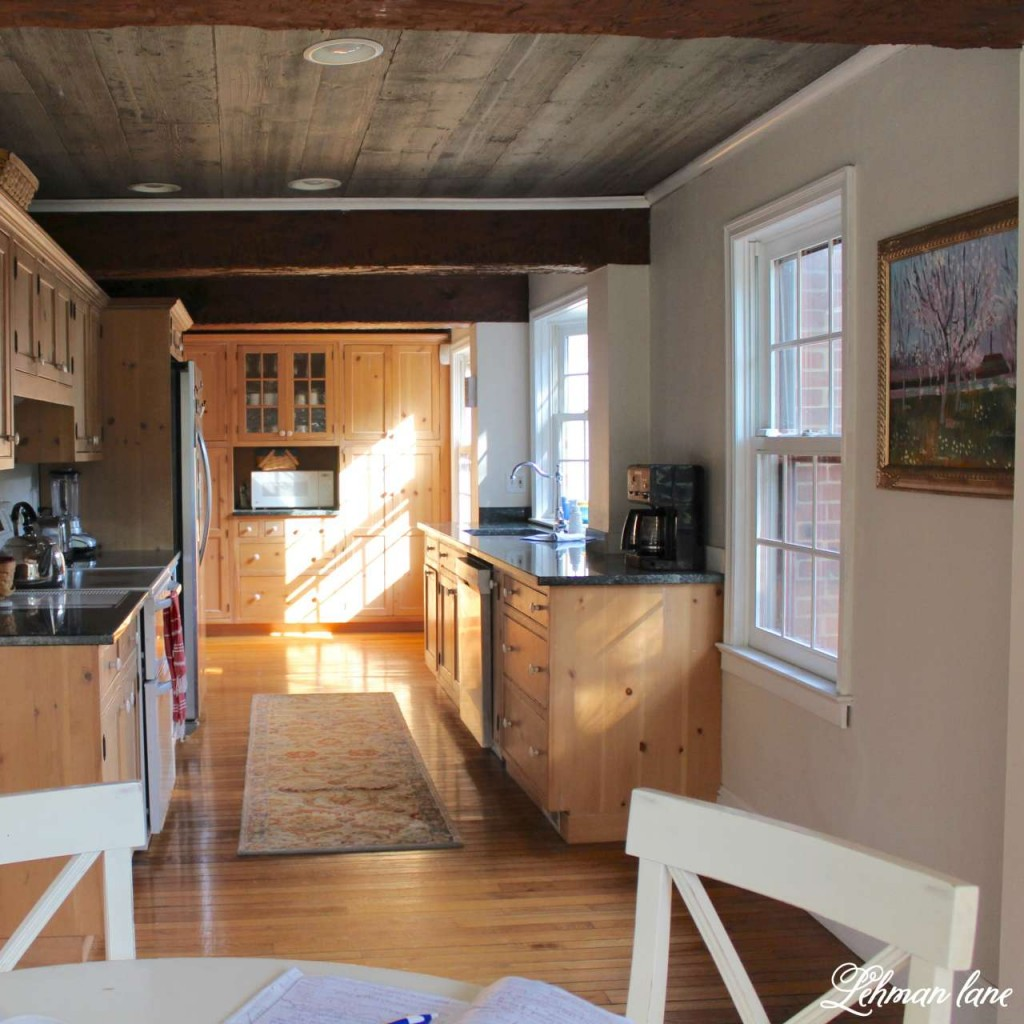 Farmhouse kitchen in SW kestral white with pottery barn runner and pine cabinets and beam ceiling
