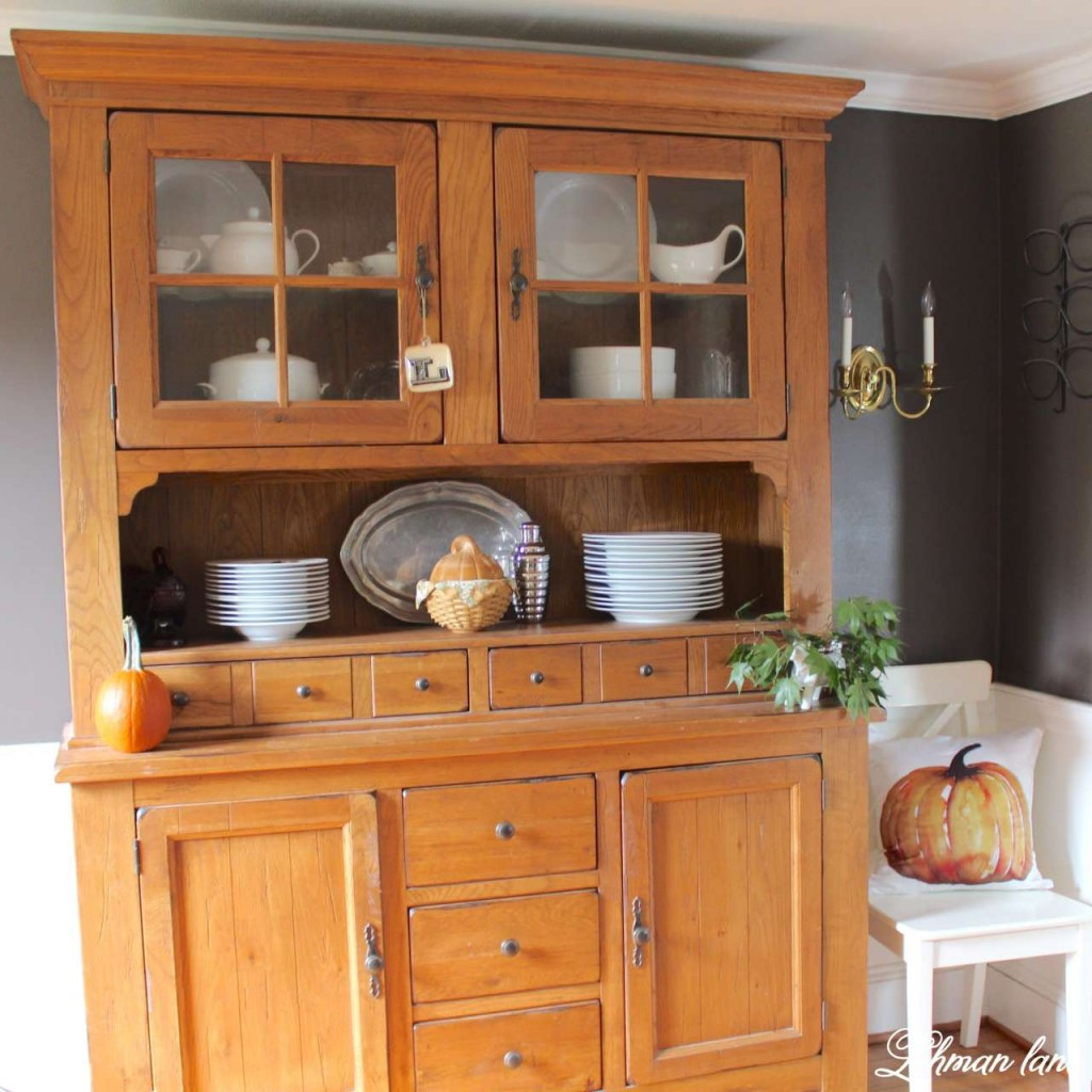 Stop by to see how we decorate our farmhouse for fall - dining room hutch with pumpkin pillow