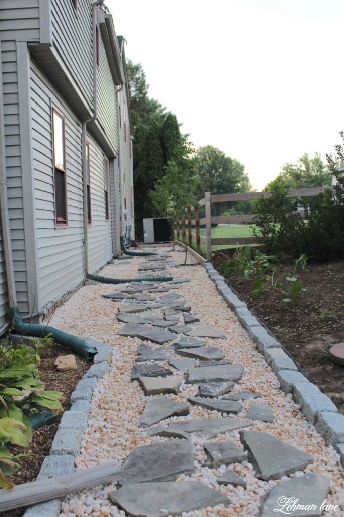flagstone and stone walkway along the back of our farmhouse next to our sunken patio