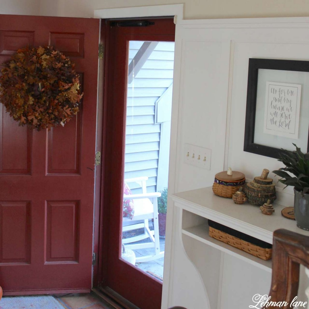 Stop by to see how we decorate our farmhouse for fall - red front doo and fall oak leaf wreath and entryway table