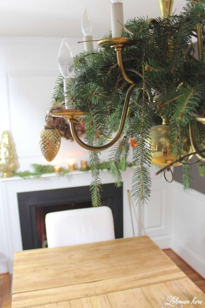 A Very Farmhouse Christmas Home Tour - chandelier evergreens and dining table