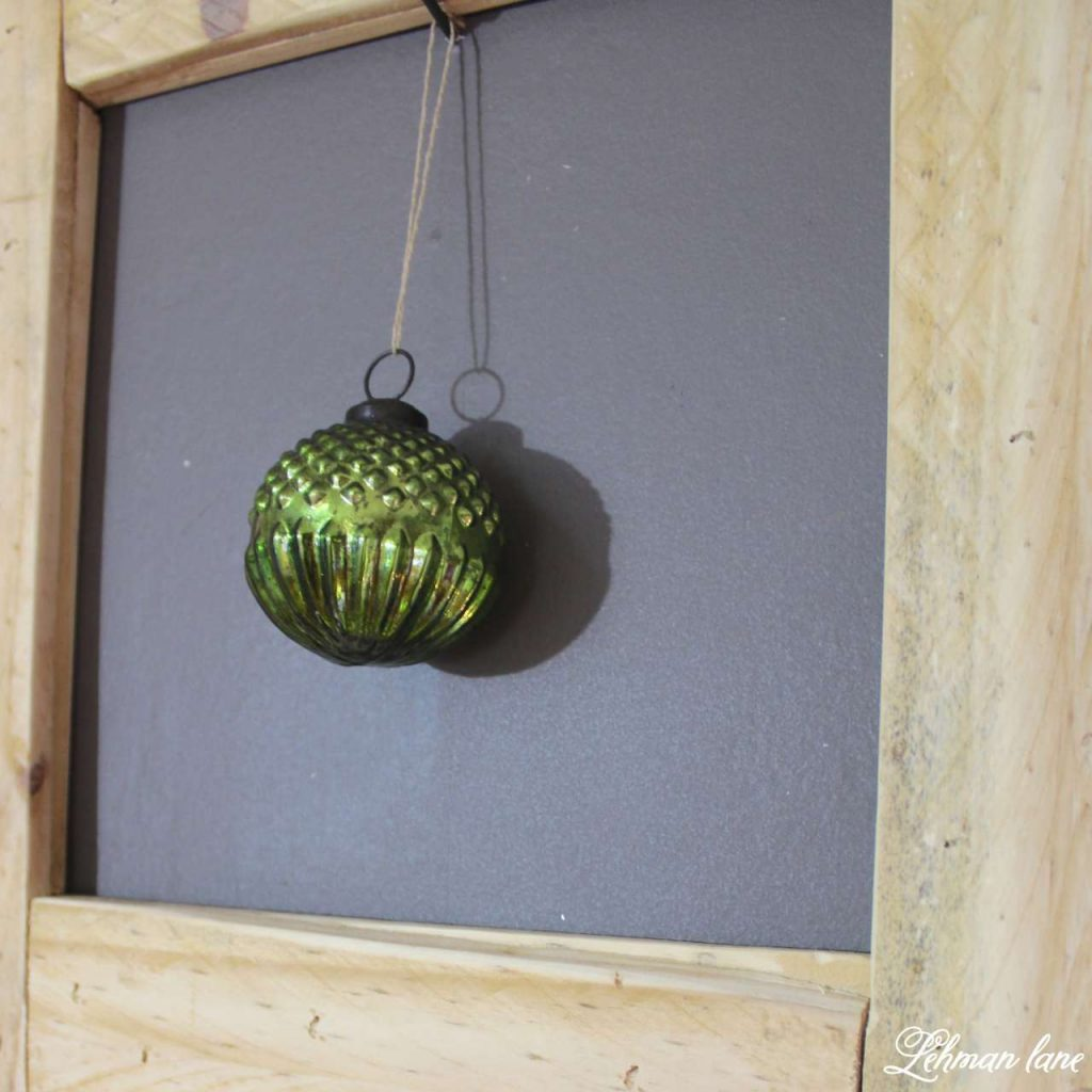 A Very Farmhouse Christmas Home Tour - pallet picture frame and Christmas ball