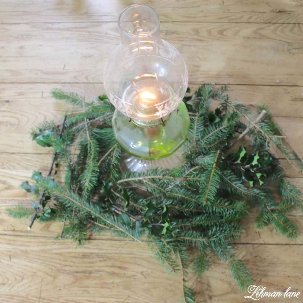 Very Farmhouse Christmas Home Tour - closeup of oil lantern and greenery on farmhouse table