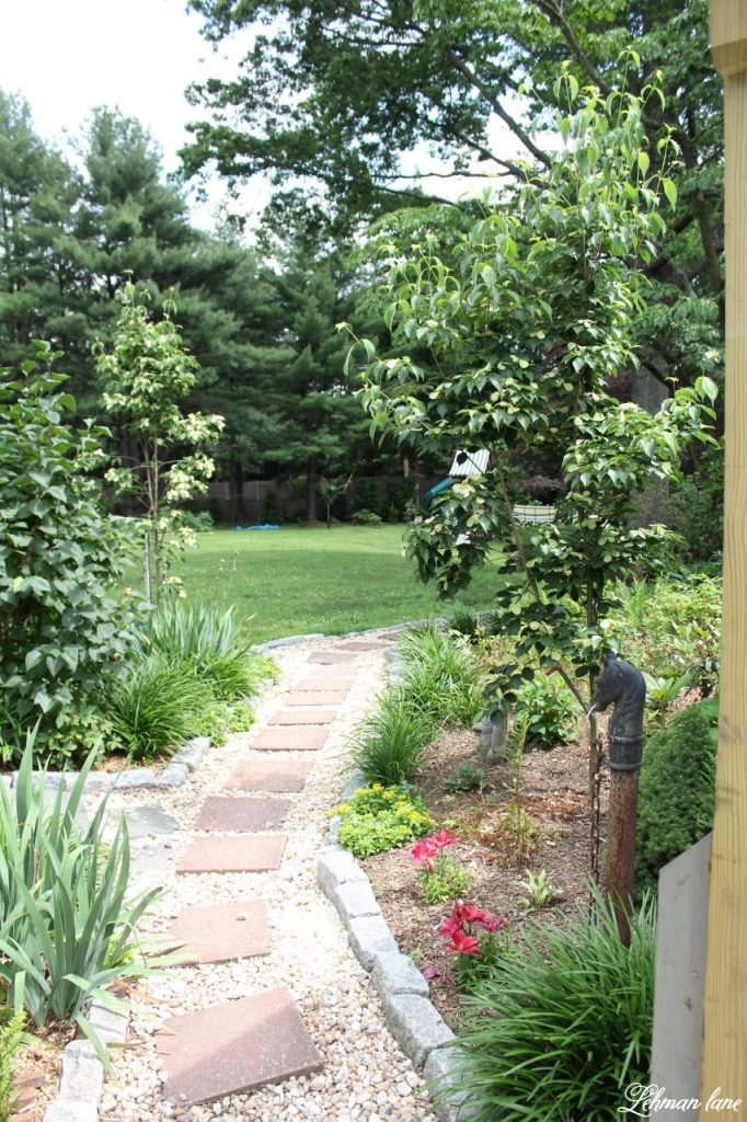 Sharing our Farmhouse's summer garden tour along with a few blogging friends for an outdoor spaces blog hop. Stop by to see summer front porches, backyard spaces, herb gardens and poolside gardens for lots of summer gardening ideas! #summer #summergarden #otdoorspaces http://lehmanlane.net / walkway garden