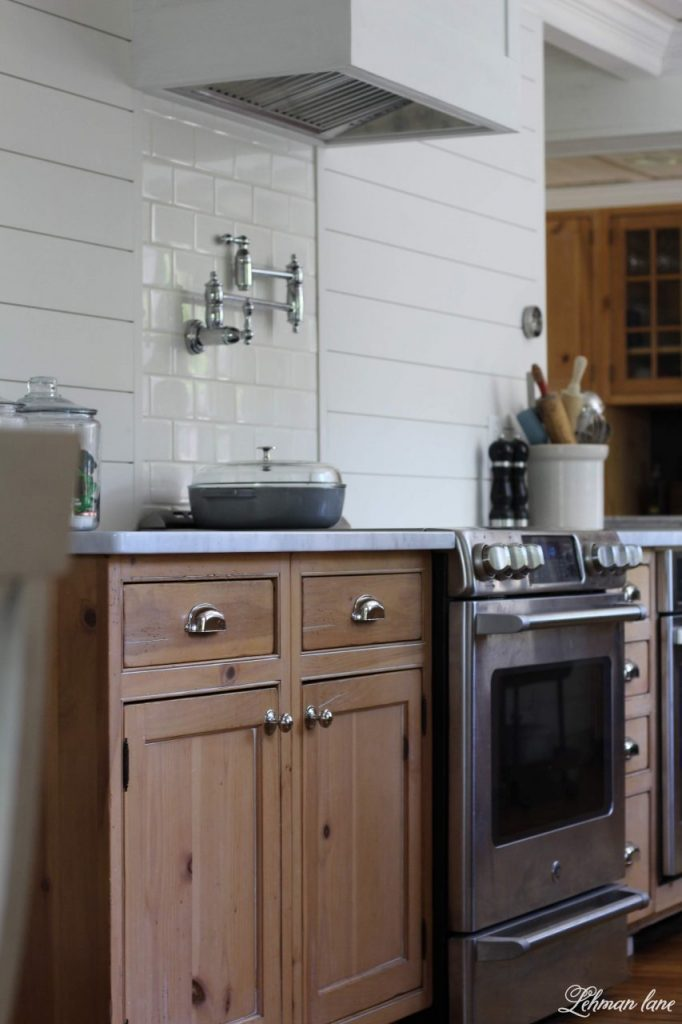DIY Wood Vent Hood We officially have a range hood for our oven! Our farmhouse kitchen previously had a useless downdraft in our countertop. Because my smoke alarm would go off sometimes when I boiled water I knew we needed a range hood. To save money we DIYed a wood range hood to cover a range hood insert. Our new hood looks so pretty and the white painted really brightens up our former dark kitchen! #venthood #farmhousekitchen #whitekitchen http://lehmanlane.net