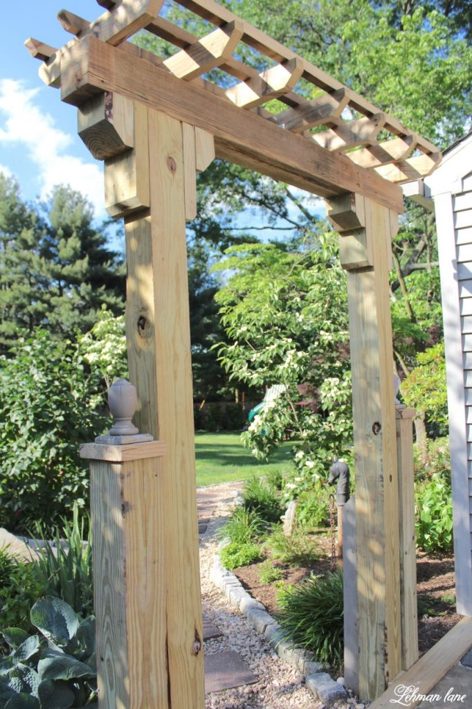 When we decided to create our sunken brick patio one thing that I really wanted to add was a wooden arbor entrance from the garden.  Our wooden arbor does a wonderful job of making this outdoor space feel more like an outdoor room.   This wooden arbor was fairly simple to make and we made it using scrap wood from the deck that we took down and wood left over from creating our wood retaining wall.