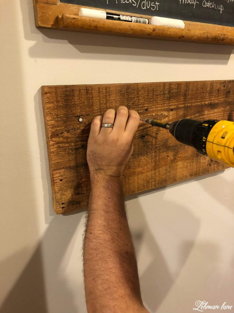 Farmhouse DIY Towel Rack - screwing the board to the wall
