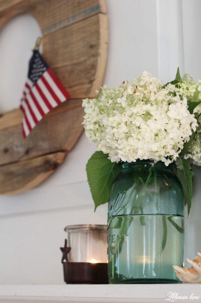 Farmhouse 4th of July Decorating is as simple as you make it. It calls for a collection of vintage & unexpected red, white & blue items from around your home, hydrangeas & of course old glory!   Sharing  ideas of how I decorate our farmhouse for free for the Independence Day! #4thofjuly http://lehmanlane.net