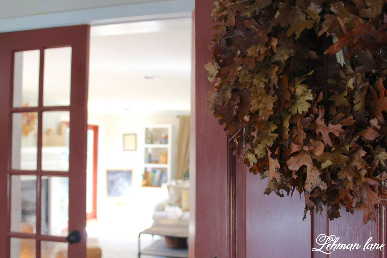 Stop by to see how we decorate our farmhouse for fall - entryway with oak leaf wreath into family room and red french door