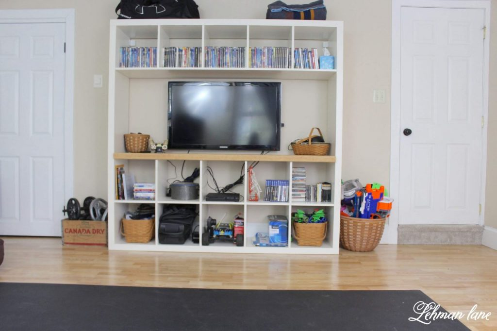 DIY Kallax Ikea Hack - We transformed our Kallax large bookcase from Ikea into a space saving Entertainment stand in just a few hours for our newly renovated home gym.  I am sharing all the details of how we DIYed this Ikea hack for only a few dollars #ikeahack  #diy https://lehmanlane.net