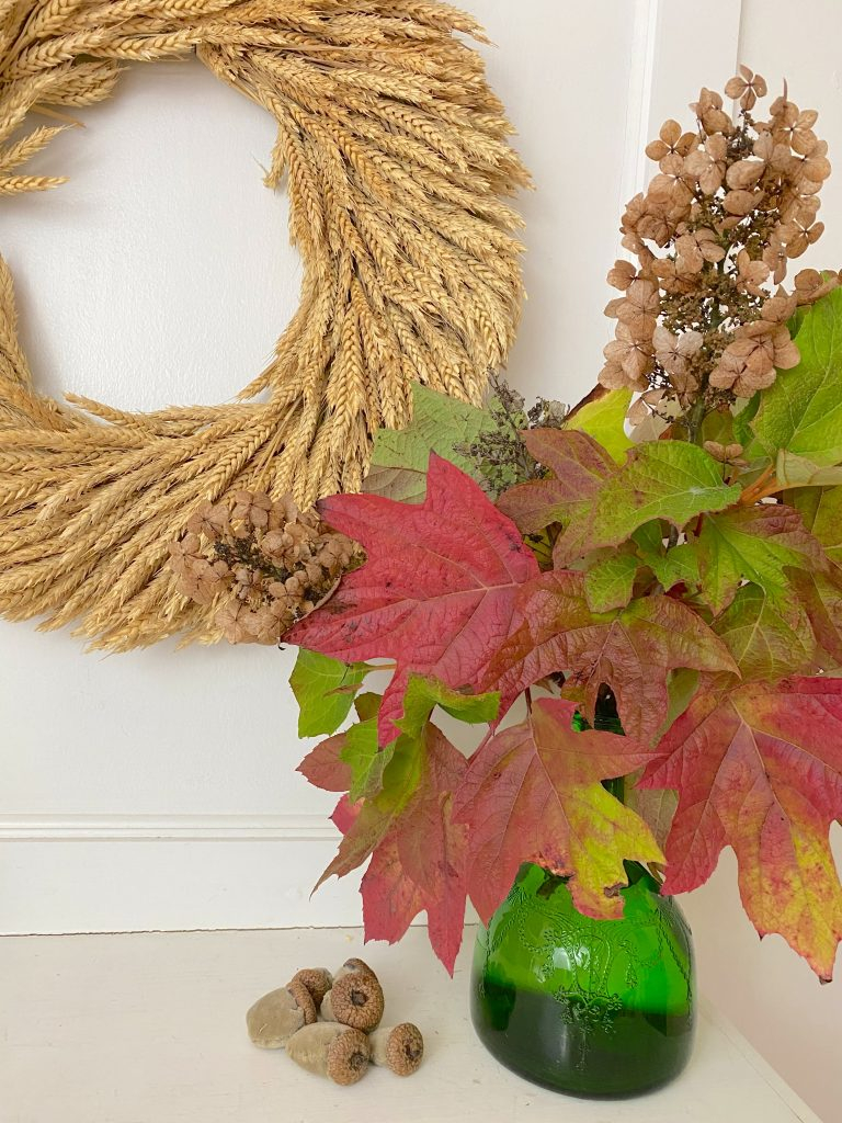 Today, I am sharing 7 colorful fall entryway decor ideas with our fall entryway table & fall decorating entryway ideas like a wheat wreath, fall printable, oakleaf hydrangea leaves, velvet acorns, baskets, pumpkin pillows on a church pew & pumpkins from our raised gardening beds. #fall #fallhomedecor #fallwreath https://lehmanlane.net