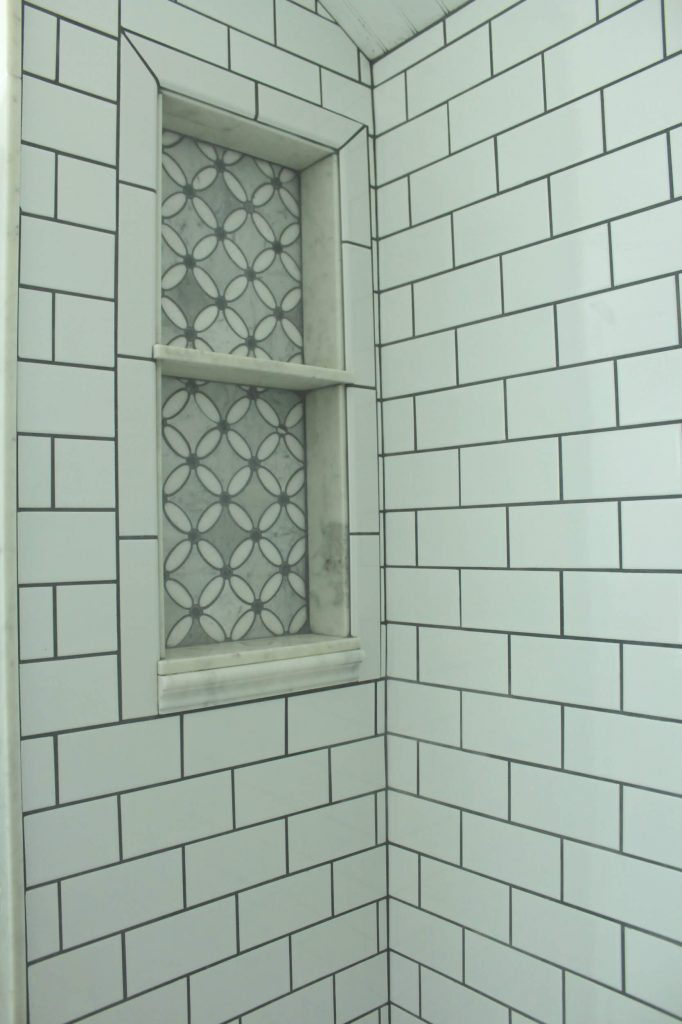 Sharing all the tips & tricks we used to create an elegant luxury master bathroom with the best master bathroom shower tile & floor combination ideas using Carrara marble, white subway tile with a marble accent wall & large Black veined marble look floor tile with grey grout & pictures! #masterbathroomtile #tileshelf #marbletile https://lehmalane.net