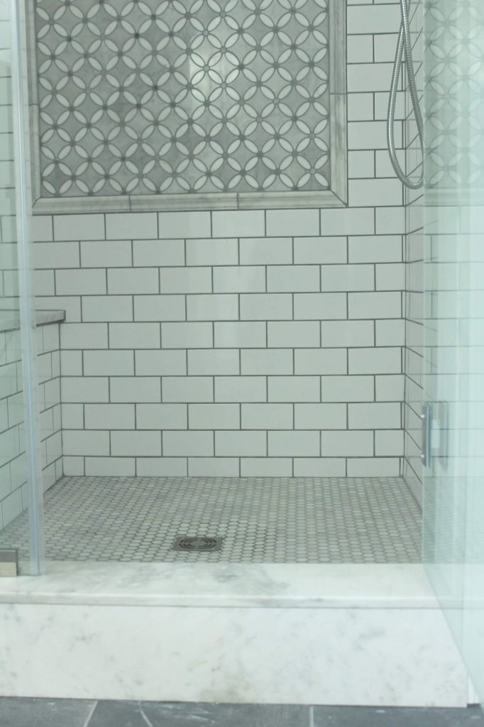 Sharing all the tips & tricks we used to create an elegant luxury master bathroom with the best master bathroom shower tile & floor combination ideas using Carrara marble, white subway tile with a marble accent wall & large Black veined marble look floor tile with grey grout & pictures!