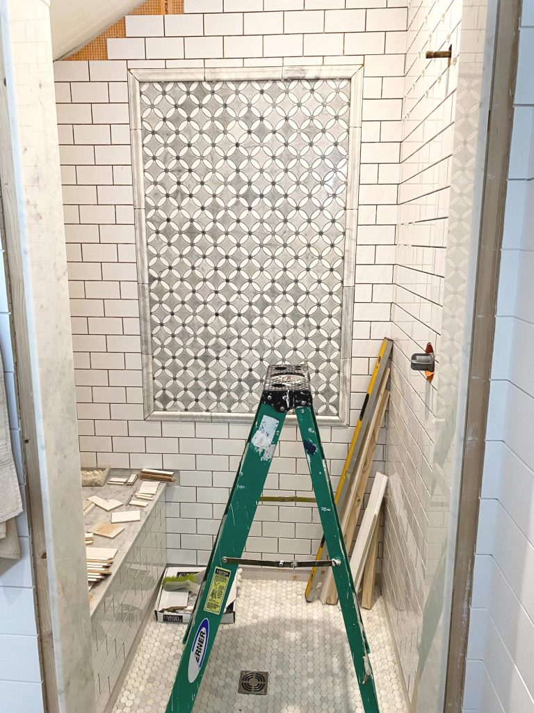 Sharing all the tips & tricks we used to create an elegant luxury master bathroom with the best master bathroom shower tile & floor combination ideas using Carrara marble, white subway tile with a marble accent wall & large Black veined marble look floor tile with grey grout & pictures! #farmhousebathroom #marbletileaccentwall #masterbathroomshowerideas https://lehmanlane.net