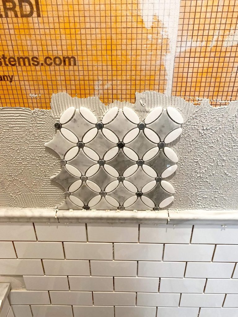 Sharing all the tips & tricks we used to create an elegant luxury master bathroom with the best master bathroom shower tile & floor combination ideas using Carrara marble, white subway tile with a marble accent wall & large Black veined marble look floor tile with grey grout & pictures! #diyproject #masterbathroomtile #marbletile https://lehmanlane.net