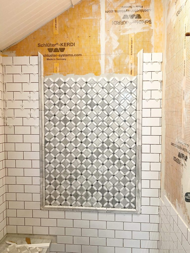 Sharing all the tips & tricks we used to create an elegant luxury master bathroom with the best master bathroom shower tile & floor combination ideas using Carrara marble, white subway tile with a marble accent wall & large Black veined marble look floor tile with grey grout & pictures! #farmhousebathroom #tileaccentwall #marble https://lehmalane.net