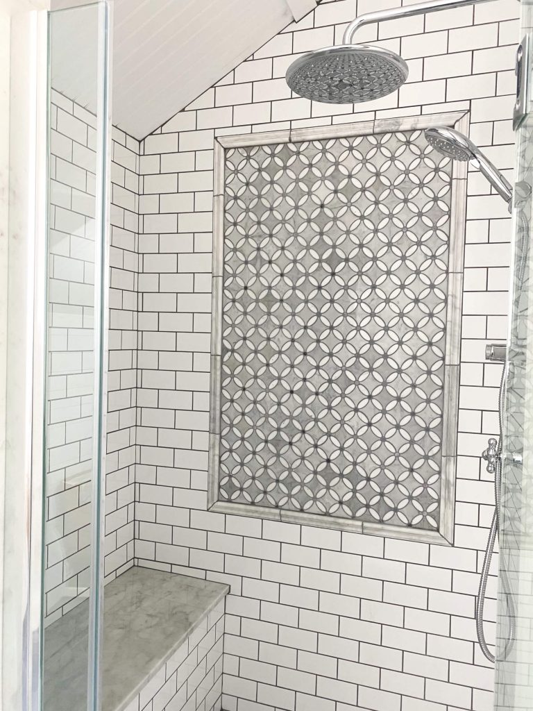 Sharing all the tips & tricks we used to create an elegant luxury master bathroom with the best master bathroom shower tile & floor combination ideas using Carrara marble, white subway tile with a marble accent wall & large Black veined marble look floor tile with grey grout & pictures! #masterbathroomshower #bathroomshowertile #marbletile https://lehmanlane.net