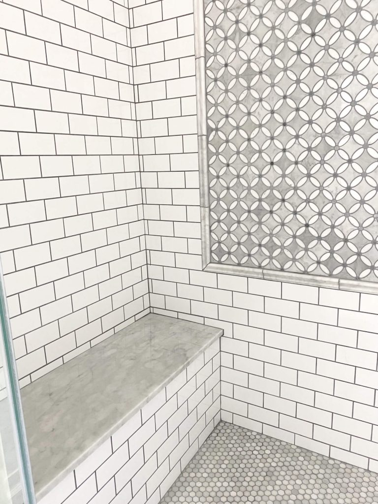 Sharing all the tips & tricks we used to create an elegant luxury master bathroom with the best master bathroom shower tile & floor combination ideas using Carrara marble, white subway tile with a marble accent wall & large Black veined marble look floor tile with grey grout & pictures! #showerseat #bathroomtile #masterbathroomshower https://lehmalane.net
