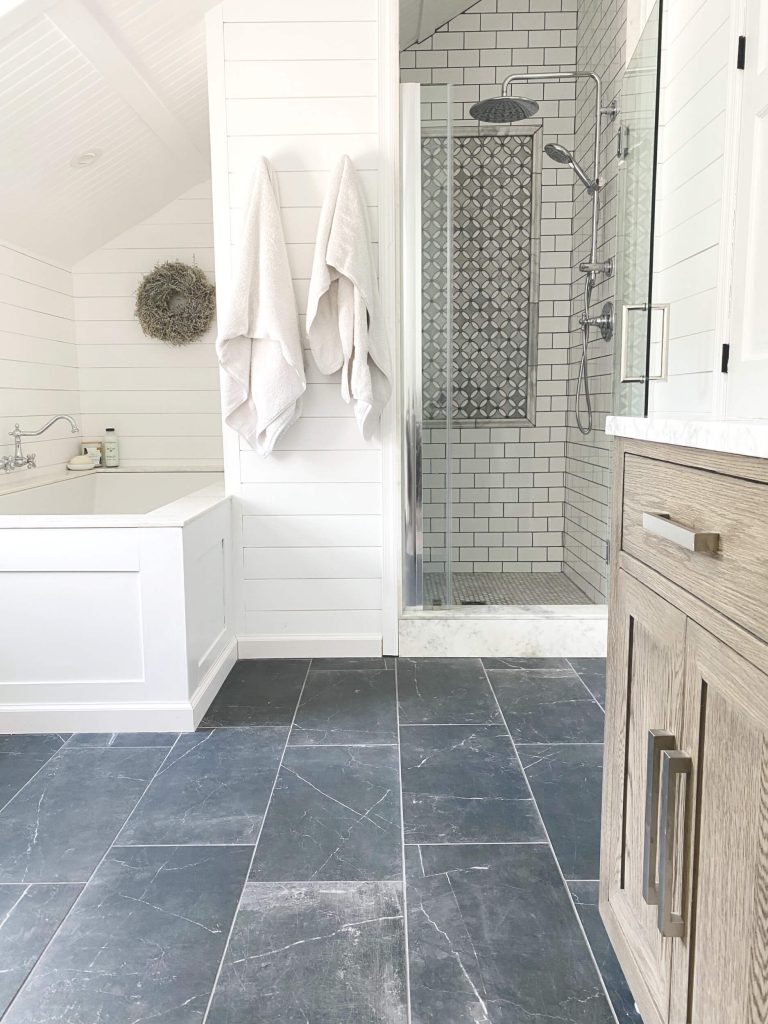 Sharing all the tips & tricks we used to create an elegant luxury master bathroom with the best master bathroom shower tile & floor combination ideas using Carrara marble, white subway tile with a marble accent wall & large Black veined marble look floor tile with grey grout & pictures! #masterbathroomshower #masterbathroomideas #farmhousemasterbathroom