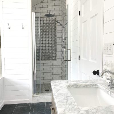 Sharing all the tips & tricks we used to create an elegant luxury master bathroom with the best master bathroom shower tile & floor combination ideas using Carrara marble, white subway tile with a marble accent wall & large Black veined marble look floor tile with grey grout & pictures! #masterbathroom #bathroomtile #farmhousebathroom https://lehmanlane.net
