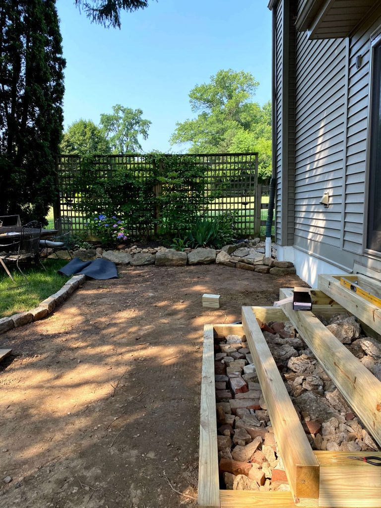 Sharing all the details of how to build an inexpensive & awesome DIY pea gravel patio for the backyard with easy DIY ideas tips & step by step before & after photos. #timberstairs #peagravelpatio https://lehmanlane.net