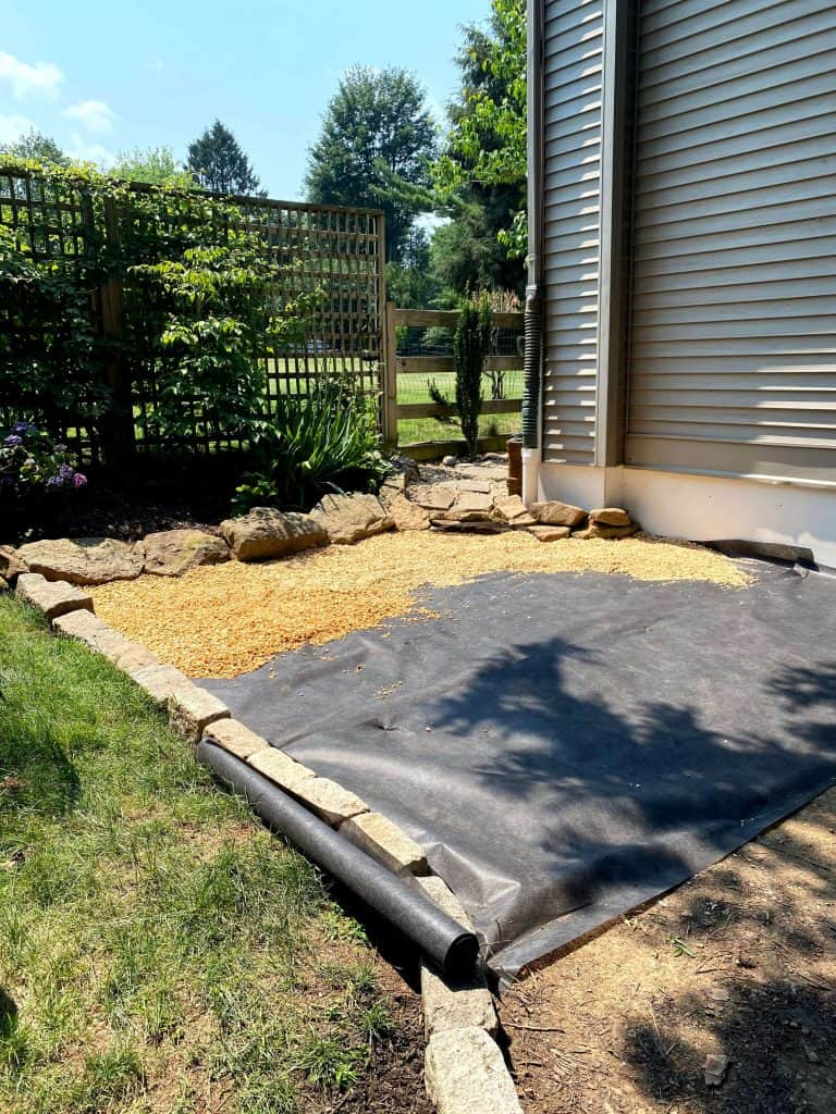 Sharing all the details of how to build an inexpensive & awesome DIY pea gravel patio for the backyard with easy DIY ideas tips & step by step before & after photos. #landscapefabric #peagravelpatio https://lehmanlane.net